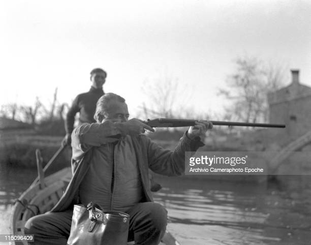 American writer Ernest Hemingway, sitting on a boat, taking aim while hunting ducks in a pond, on Torcello island, Venice, 1948. Hemingway is using a...