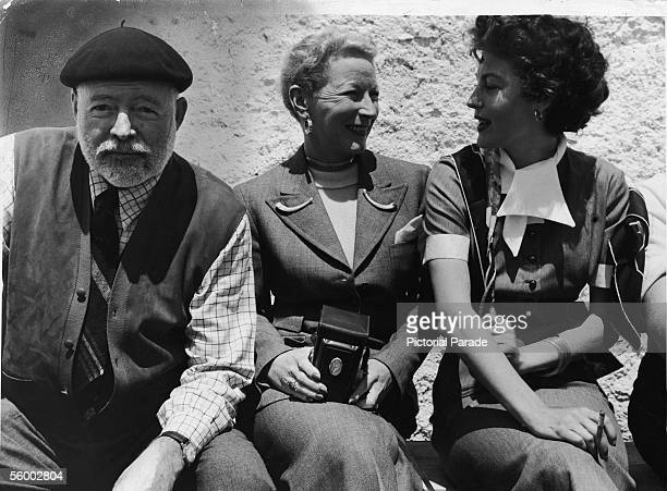 American writer Ernest Hemingway smiles at the camera while his fouth wife journalist Mary Welsh Hemingway and actress Ava Gardner sit nearby and...