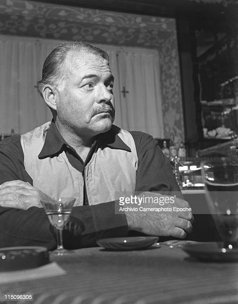 American writer Ernest Hemingway, wearing a hunter waistcoat portrayed sitting at a table, with a glass in front of him, Venice, 1948.