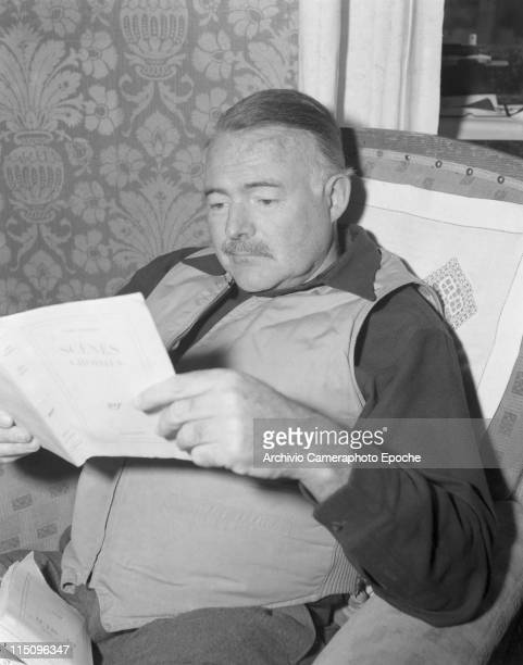 American writer Ernest Hemingway wearing a hunter waistcoat sitting on an armchair reading a book another book on his knees Cortina d'Ampezzo 1948