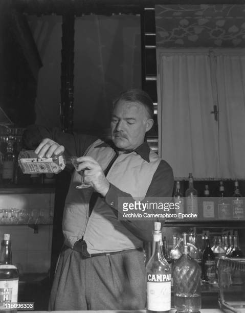 American writer Ernest Hemingway wearing a hunter waistcoat, standing behind a bar counter and pouring gin from a bottle of Gordon's, other alcoholic...