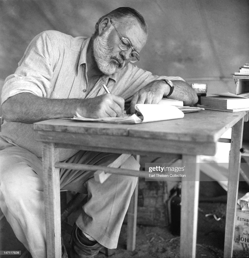 American writer Ernest Hemingway (1899 - 1961) working at a portable table while on a big game hunt in Kenya, September 1952.