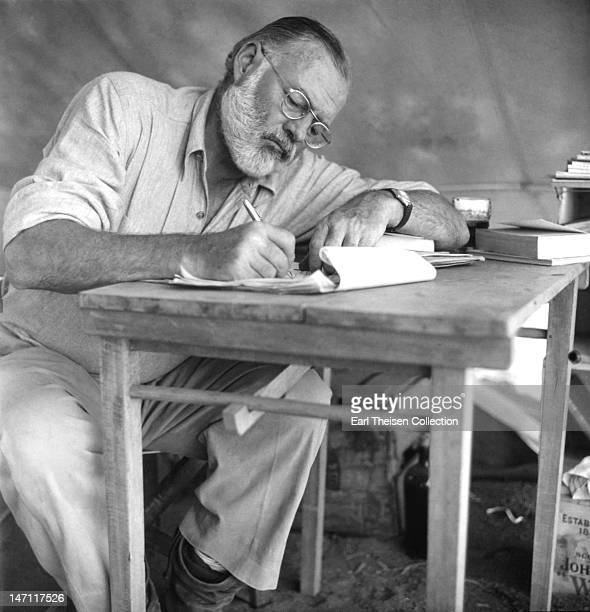 American writer Ernest Hemingway working at a portable table while on a big game hunt in Kenya, September 1952.