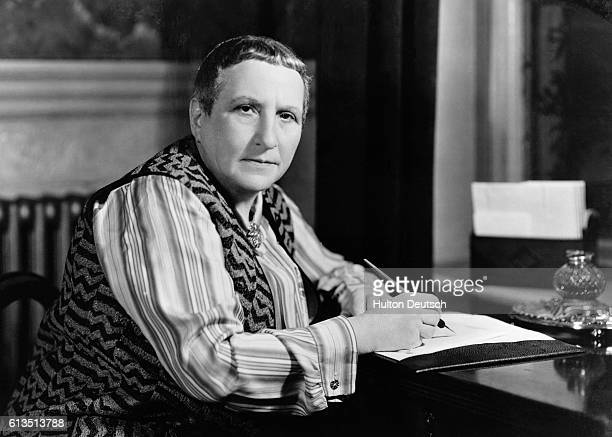 American writer Gertrude Stein sits at her desk She settled in Paris to experiment in arts and letters during the early 1900s surrounded by prominent...