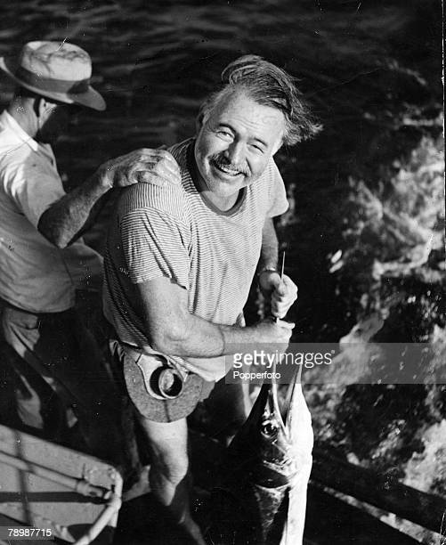 American writer of novels and short stories Ernest Hemingway pictured with his catch while on a fishing trip, circa 1945.