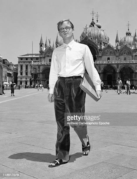 American writer Truman Persons 'Capote' wearing glasses a withe shirt velvet trousers and sandals holding a folder walking around in St Mark Square...