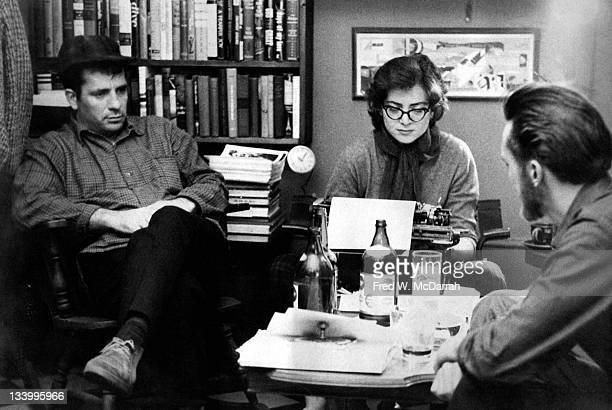 American writers Jack Kerouac and Lew Welch sit around a low table as they collaborate on a poem which is typed by Gloria Schoffel in the apartment...