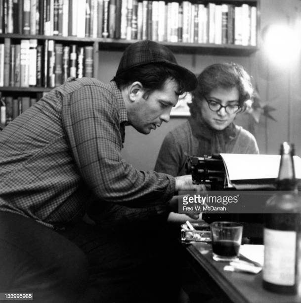 American writers Jack Kerouac makes a suggestion to Gloria Schoffel in the apartment of her and her soontobe husband photographer McDarrah New York...