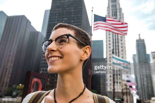American Young woman in downtown Chicago and US flag