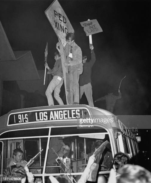 American youths wielding roadsigns - with one holding a placard reading 'Stamp out LAPD' - as they stand on the roof of a Rapid Transit bus during...