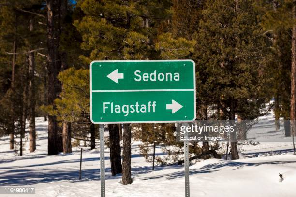Americana Roadside America shows Sign to Flagstaff and Sedona in snow.