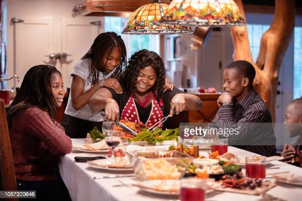 american-african family at table during thanksgiving dinner - canadian thanksgiving stock pictures, royalty-free photos & images
