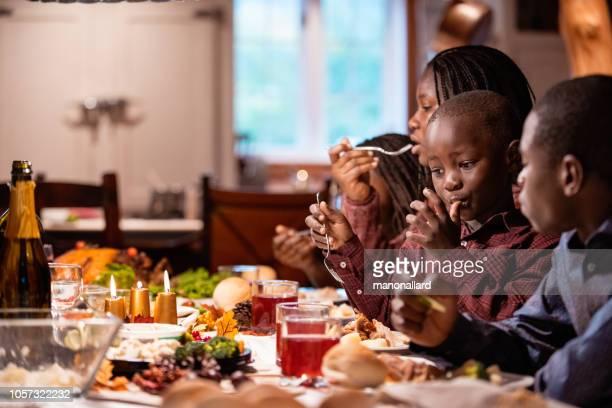 africano-americano família na mesa durante o jantar de ação de graças - african american family dinner - fotografias e filmes do acervo