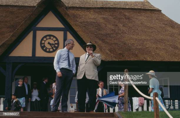 Americanborn British philanthropist Sir Paul Getty shows his new cricket ground to British Prime Minister John Major during the first match to be...