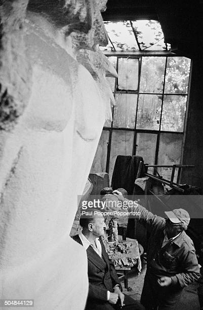 Americanborn British sculptor Jacob Epstein working on a bust of his sitter British writer William Somerset Maugham 1951