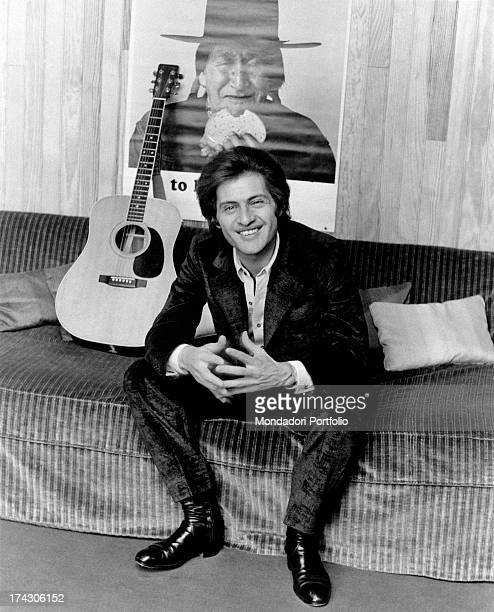 Americanborn French singer Joe Dassin smiling on a sofa beside a guitar Behind him a poster portraying an American Indian Paris 1970s