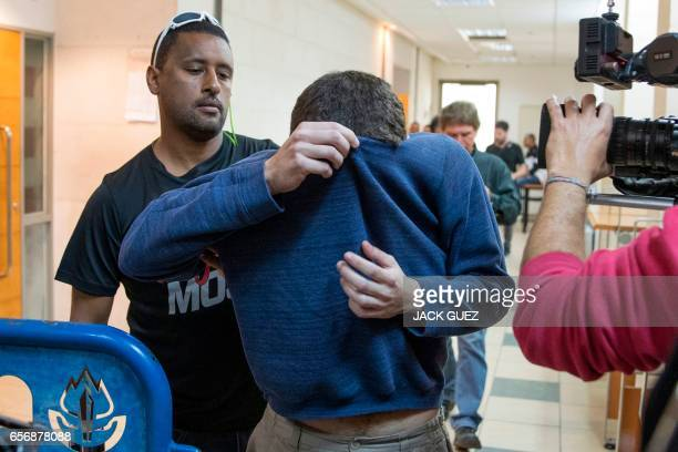 AmericanIsraeli Jewish teenager Michael Kadar accused of making dozens of antiSemitic bomb threats in the United States and elsewhere is escorted by...