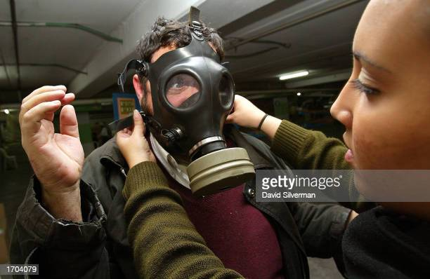 American-Israeli Michael Satious who moved to Israel from Los Angeles four years ago, is directed by an Israeli soldier on how to use his gas mask at...
