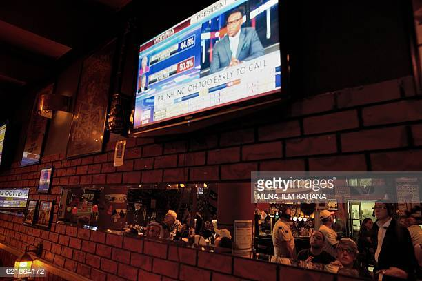 Americans and Israelis watch a live TV report of the US presidential election's results at Mike's place bar in Jerusalem on November 9 2016...