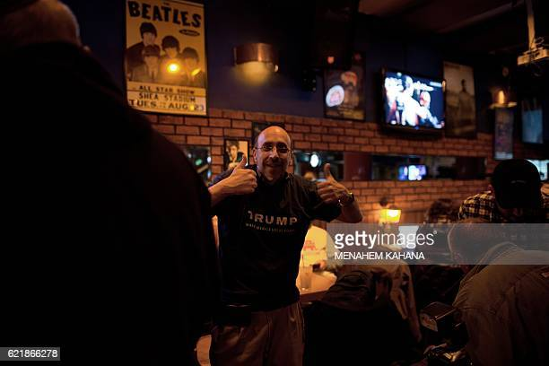 Americans and Israelis watch live TV reports of the US presidential election's results at Mike's place bar in Jerusalem on November 9 2016...