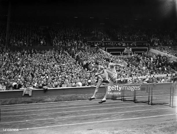 Americans Bill Porter and Clyde Scott leading midway in the Men's 110 metres Hurdles final at Wembley Stadium during the London Olympic Games 4th...