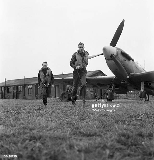 The Work Of No 121 Squadron RAF Rochford Essex August 1942 Flying Officer Barry Mahon and Flight Lieutenant Seldon R Edner run to their aircraft as...