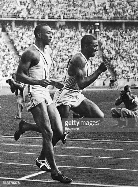 Americans Jesse Owens and Ralph Metcalfe during the 400meter relay at the 1936 Olympic Games in Berlin