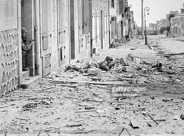 Americans take shelter during mop-up of Brest. Crouching behind a pile of rubble, a U. S. Soldier watches for German snipers in the streets of Brest,...