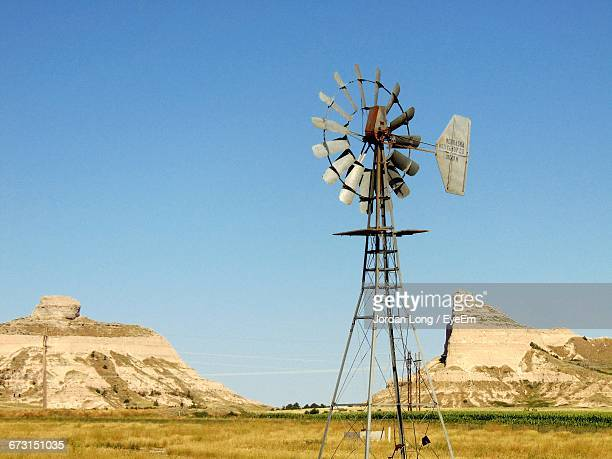 american-style windmill on field against clear blue sky - american style windmill stock pictures, royalty-free photos & images