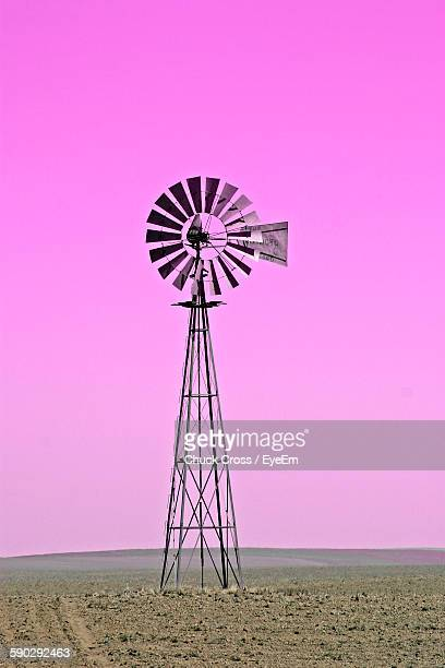 American-Style Windmill On Field Against Pink Sky