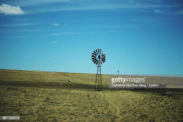 American-Style Windmill On Grassy Field Against Sky