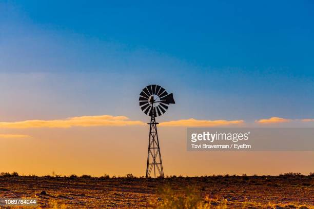 american-styled windmill on field against sky during sunset - american style windmill stock pictures, royalty-free photos & images