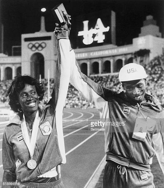 America's Al Joyner who won Gold in the Triple Jump 8/4 raises hand of his sister, Jackie who won a Silver in the Women's Heptathalon.