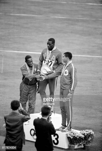 America's Bob Hayes winner of the gold medal in the Olympic 100meter dash is flanked by silver medalist E Figerola of Cuba and bronze medal winner...