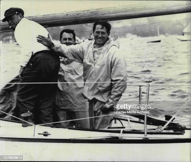 America's Cap Skipper Jock Stunock waves happily from the tiller of Victorian 36ft sloop Julie ofter the start January 04 1963
