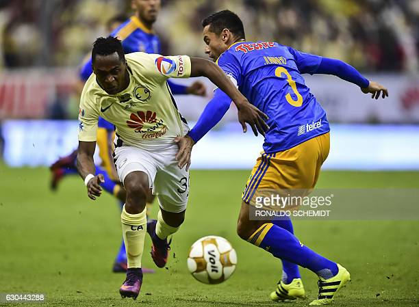 America´s Carlos Quintero vies for the ball with Tigres' Juninho during their Mexican Apertura 2016 tournament final first leg football match at the...