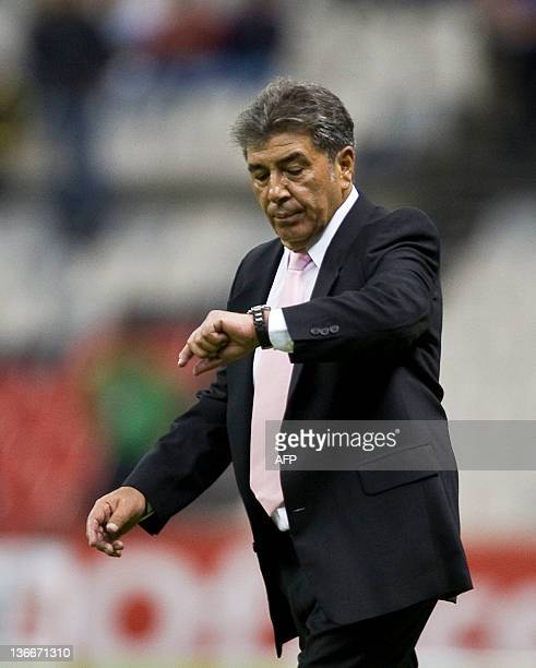 America´s coach Carlos Reinoso looks at his watch following a match against San Luis during their Mexican Apertura tournament in Mexico City on...
