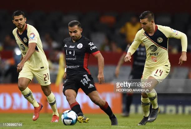America's Colombian midfielder Nicolas Benedetti vies for the ball with Lobos Buap's Chilean mifielder Bryan Rabello during their Mexican Clausura...