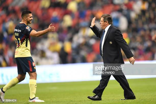 America´s forward Josue Martin Henry celebrates with his coach MIguel 'El Piojo' Herrera after scoring a goal against Lobos Buap during their Mexican...