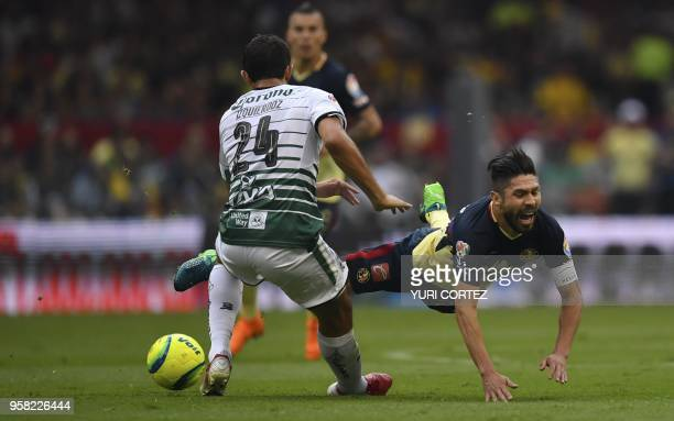 America's forward Oribe Peralta vies for the ball with Santos' defender Carlos Izquierdoz during their semifinal secong leg football match of...