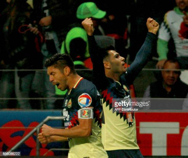America's forward Silvio Romero celebrates with teammate forward Oribe Peralta after scoring the first goal against Toluca during their Mexican...