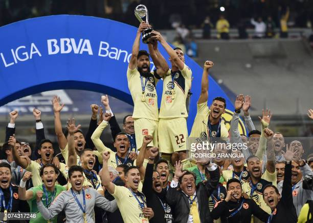 America's players celebrate with the trophy after defeating Cruz Azul to win the Mexican Apertura Tournament football final at the Azteca stadium in...