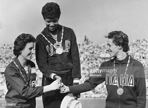 America's Wilma wears her gold medal as she stands on the podium in the awards ceremony after winning the women's dash here Slept 2nd At left is...