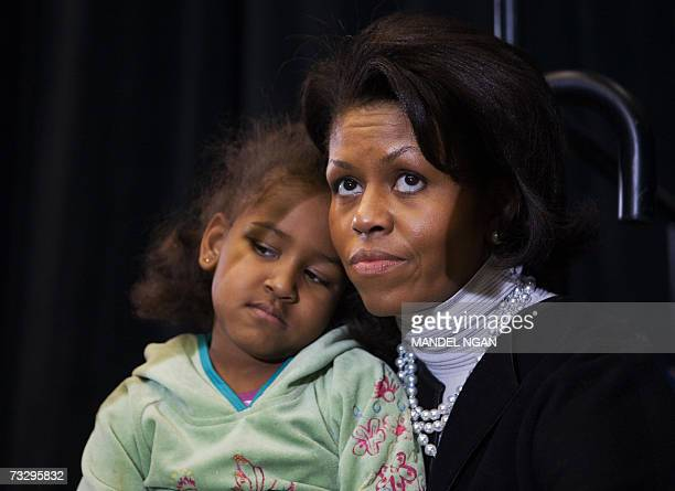 Michelle Obama, the wife of presidential hopeful Senator Barack Obama, D-IL, and their daughter Sasha listen as Obama speaks during a rally 11...