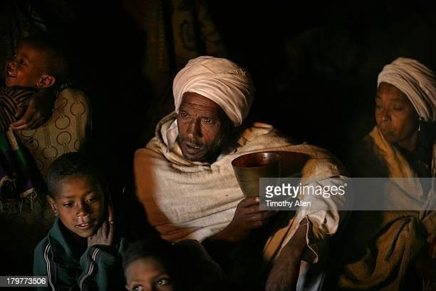 Amharic family drink tea in dark hut in mountains