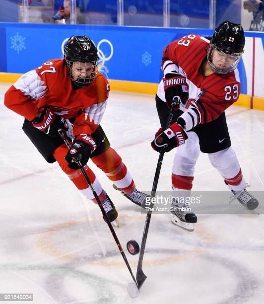 Ami Nakamura of Japan and Stefanie Wetli of Switzerland compete for the pack during the Women's Ice Hockey Classification game on day eleven of the...