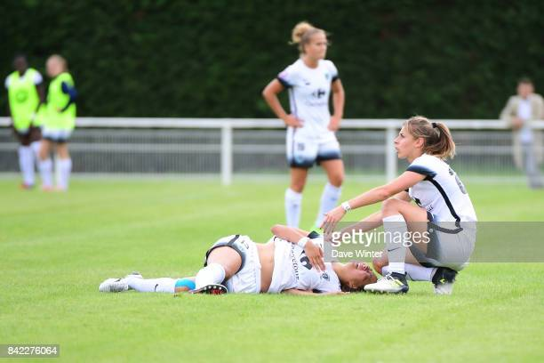 Ami Otaki of Paris FC goes down injured and is assisted by Camille Catala of Paris FC during women's Division 1 match between FC Fleury 91 and Paris...