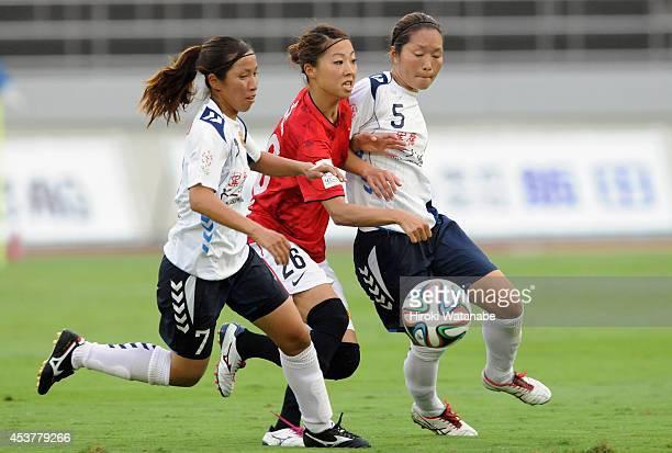 Ami Otaki of Urawa Reds Emi Nakajima and Junko Kai of INAC compete for the ball during the Nadeshiko League match between Urawa Red Diamonds Ladies...