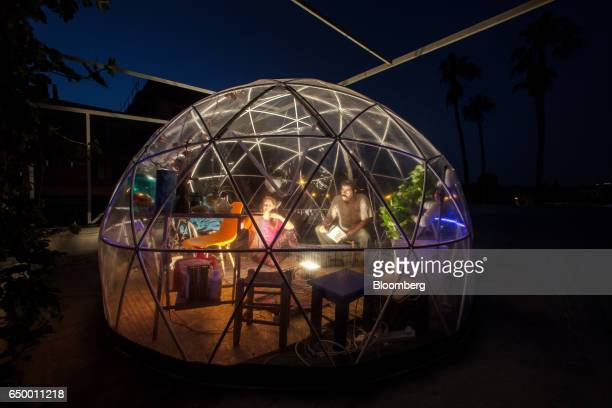 Amichai Yifrach cofounder and chief technology officer of FluxIoT right and Karin Kloosterman cofounder of FluxIoT sit in a pop up plastic greenhouse...