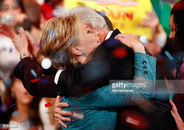 Amid falling confetti Democratic presidential hopeful Sen Hillary Clinton is embraced by former US president Bill Clinton during a primary night...